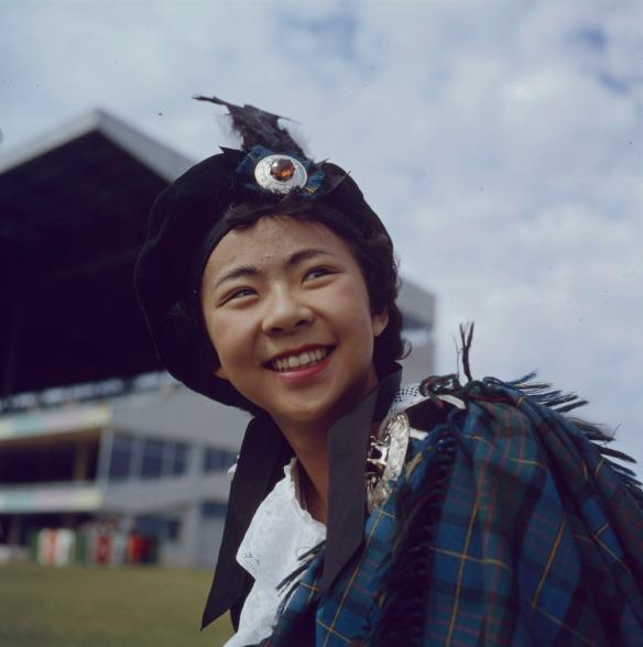 Photo en couleurs d'une fillette souriant, portant un béret écossais et une pièce d'étoffe en tartan à l'épaule.