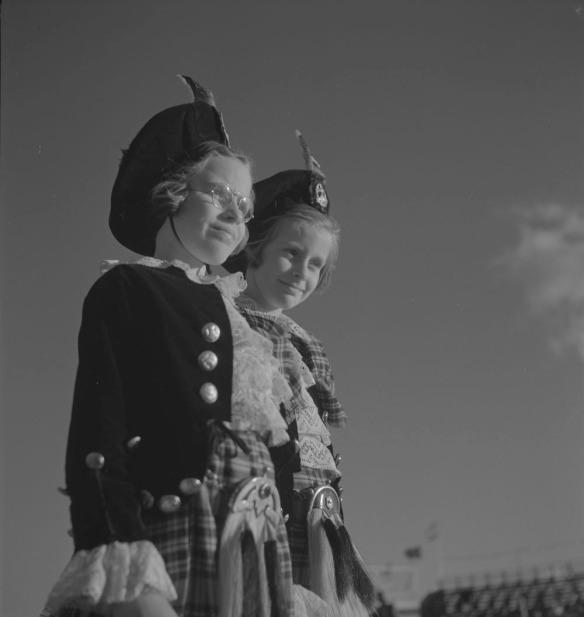 Photo noir et blanc de deux fillettes debout, portant des bérets écossais ainsi que des kilts et des vestes assortis.