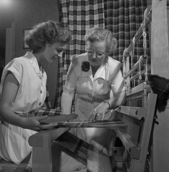 Photo noir et blanc de deux femmes devant un métier à tisser. La femme assise à gauche tient la navette. La femme debout à droite examine le motif et le tissage d'un tartan.