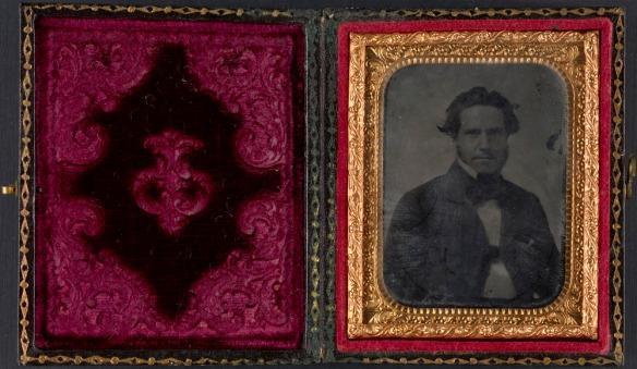 Image couleur d'un coffret en papier tapissé de velours rouge. Sur le côté droit, une photo en noir et blanc encadrée par un passe-partout de cuivre représente un jeune homme vêtu d'un veston de couleur foncée.