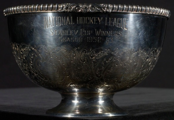 Une photo en couleurs d'un bol de cuivre plaqué argent sur lequel est gravé « National Hockey League, Stanley Cup Winners, Season 1952–53 » [Ligue nationale de hockey, gagnants de la coupe Stanley, saison 1952-1953].