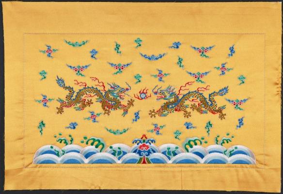 Une broderie dorée de deux dragons dont les griffes sont pointées vers une perle; ils volent parmi les nuages, au-dessus des vagues de l'océan.
