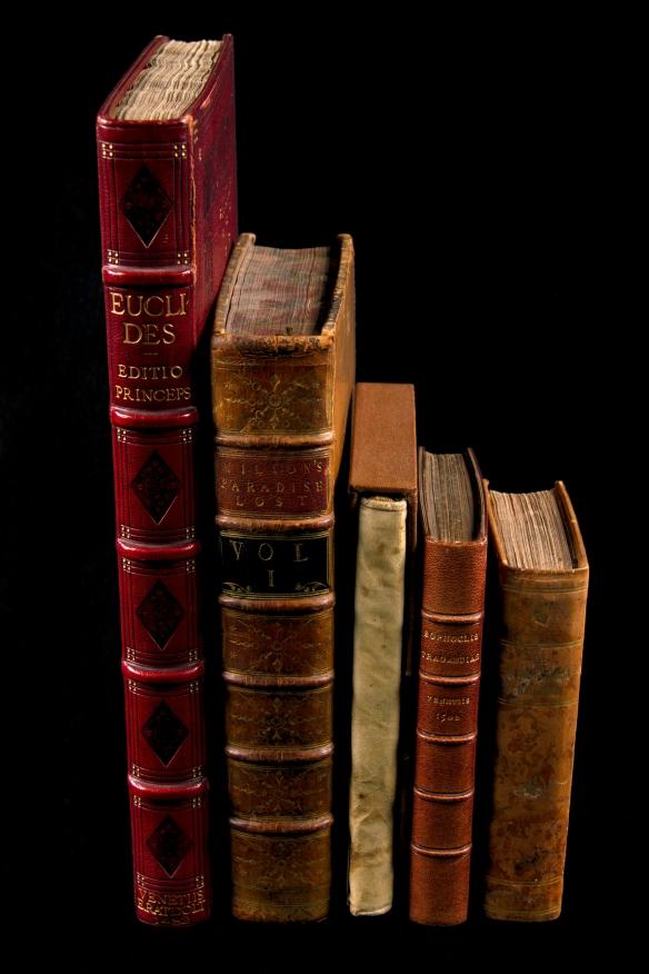 Photo en couleur - RRangée de livres (de gauche à droite : Éléments d'Euclide, 1482; Paradise Lost de Milton, 1758; Relation de ce qui s'est passé en la mission des Pères de la Compagnie de Jésus …, 1651; Sophocleos Tragoediai, 1502; The Lower-Canada Watchman, 1829)