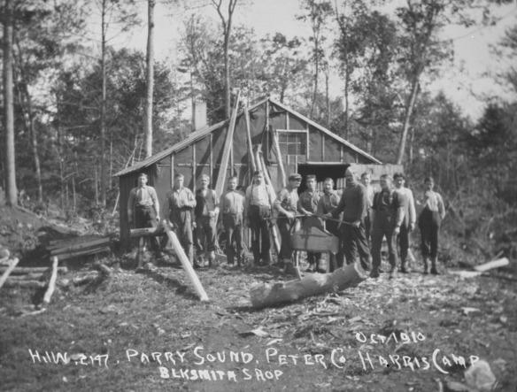 Photographie en noir et blanc de treize hommes prenant la pose devant la forge.