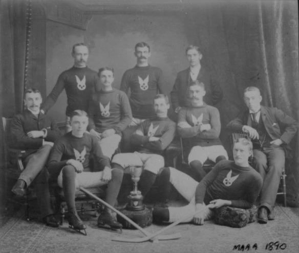 Photographie en noir et blanc montrant un groupe d'hommes debout, assis ou allongés. La plupart portent un uniforme d'équipe et des patins de hockey.