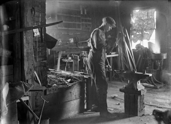 Photographie en noir et blanc d'un homme forgeant un morceau de métal à la forge Jolly.