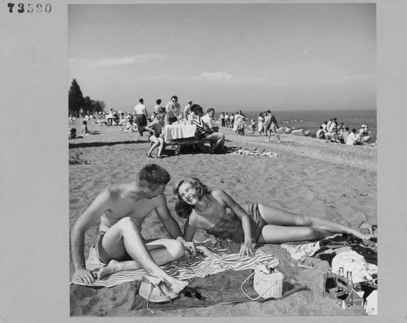 Photo noir et blanc de Kathleen Hart et Dave Phipps prennent un bain de soleil sur la plage.