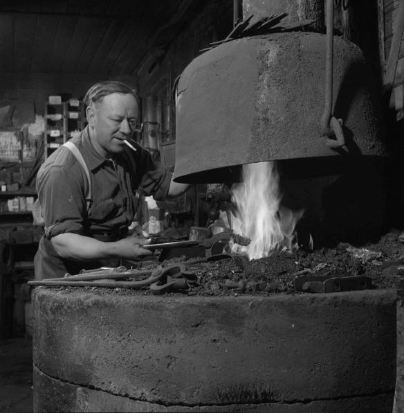 Photographie en noir et blanc d'un homme chauffant un fer à cheval dans une forge.