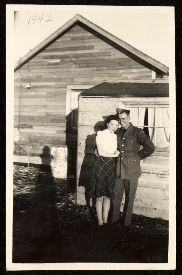 Photographie en noir et blanc d'un militaire en uniforme, le bras autour d'une jeune femme vêtue d'une robe fleurie, devant une maison de planches.
