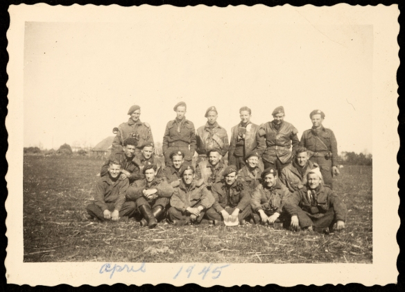 Photographie en noir et blanc d'un groupe de 18 soldats en uniforme, dans un champ cultivé.