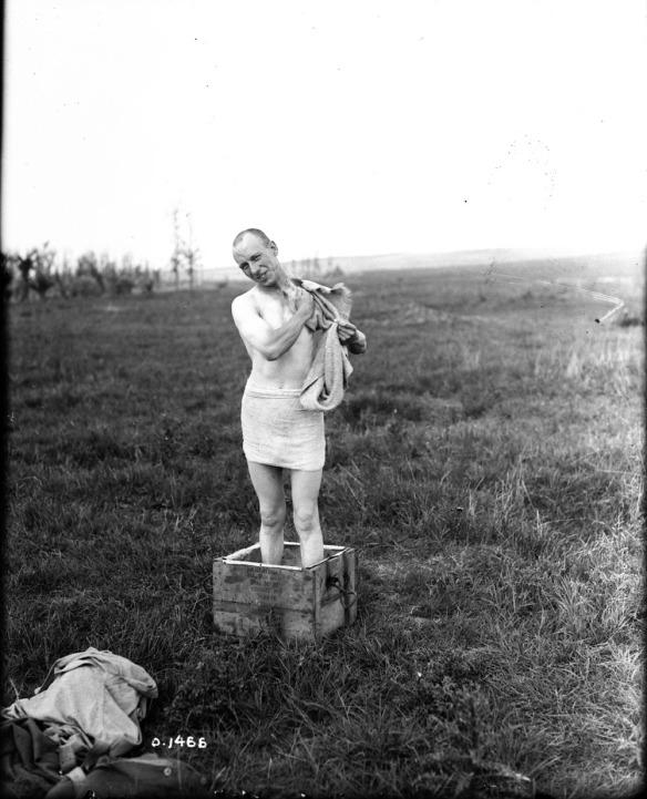 Photo noir et blanc d'un homme debout se lavant dans un bain mobile de l'époque de la Première Guerre mondiale.