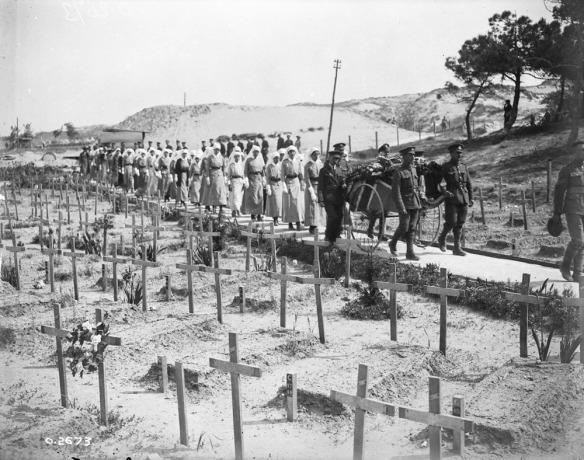 Photo noir et blanc d'un cortège funèbre de soldats et d'infirmières militaires marchant derrière un chariot-brancard sur lequel est déposé un cercueil drapé d'un drapeau, au milieu d'un grand cimetière hérissé de croix tombales temporaires.