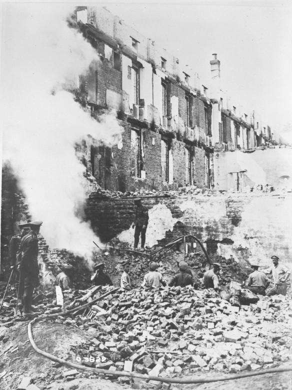 Photo noir et blanc de soldats en uniforme travaillant au milieu des décombres d'un grand bâtiment de briques lourdement endommagé par un bombardement.