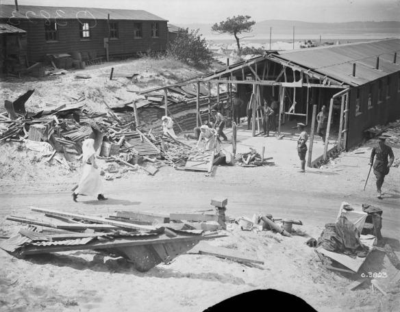 Photo noir et blanc d'infirmières militaires et de soldats en uniforme dégageant les débris d'un hôpital endommagé.