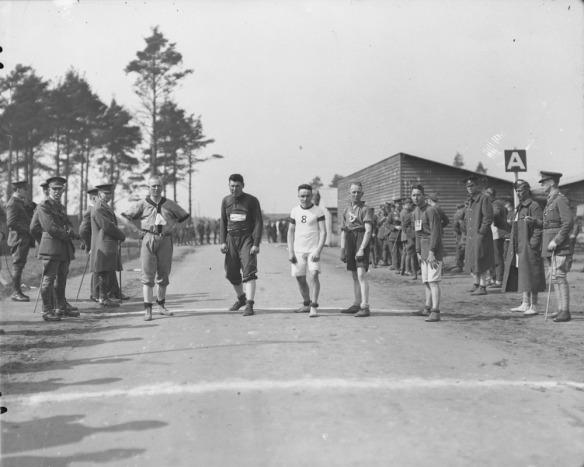 Une photographie noir et blanc de cinq hommes alignés sur une route, prêts pour le départ d'une course. Des soldats debout de chaque côté de la route les regardent.
