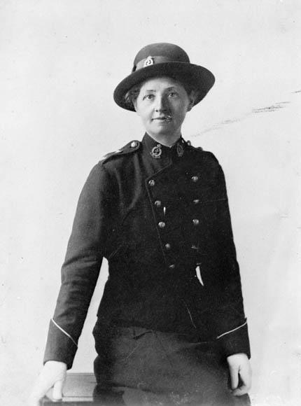 Portrait noir et blanc de studio d'une infirmière militaire en uniforme coiffée d'un chapeau, s'appuyant contre une table.