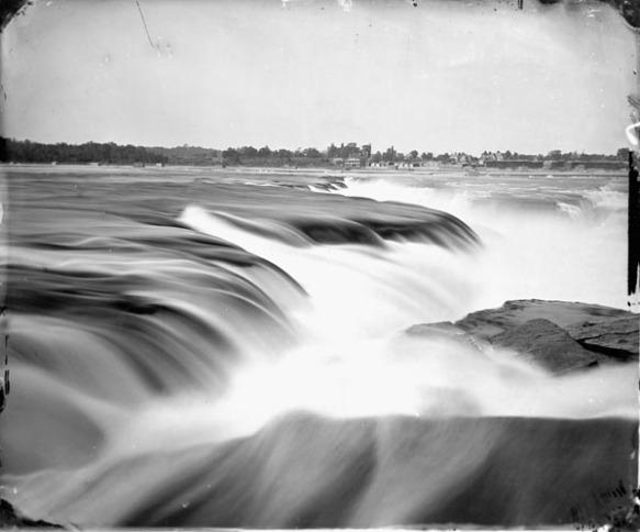 Photo noir et blanc d'un gros plan des chutes de la Chaudière avec des bâtiments visibles sur la rive éloignée.
