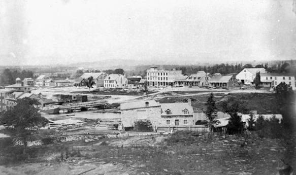 Photo noir et blanc d'une ville peu peuplée avec quelques bâtiments en arrière-plan.
