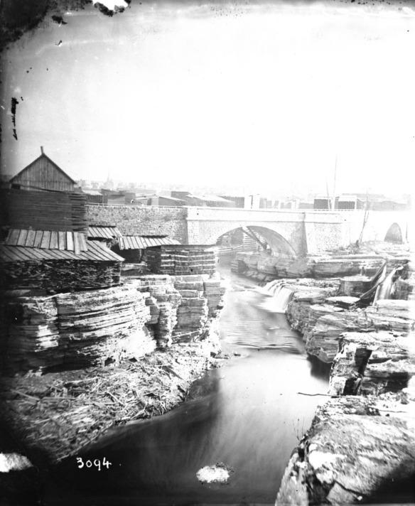 Photo noir et blanc d'un paysage riverain industrialisé montrant un pont, des roches striées et des bâtiments en arrière-plan.
