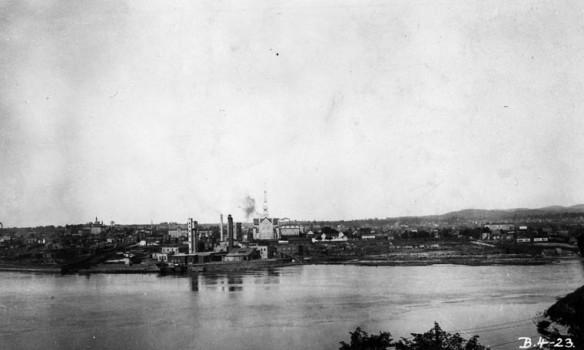 Photo noir et blanc de la rive d'une rivière où se trouve un complexe de fabrication. Une grande église se trouve sur la colline en arrière-plan.