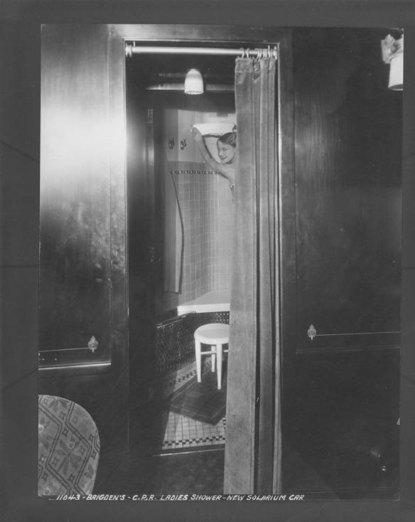 Photo noir et blanc d'une douche pour femmes dans la voiture avec solarium d'un train des Chemins de fer Canadien Pacifique.