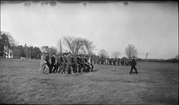 Photographie en noir et blanc d'un champ où un groupe d'officiers, à l'avant-plan, suivent leur commandant tandis que d'autres officiers en ligne sont au garde-à-vous, à l'arrière-plan.
