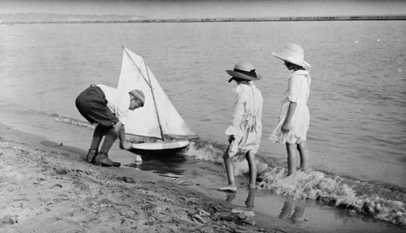 Une photographie noir et blanc de deux fillettes observant un garçon mettre à l'eau un voilier miniature.