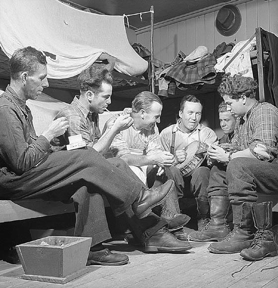 Photo noir et blanc d'un groupe d'hommes assis dans un pavillon-dortoir, jouant de la musique et fumant.
