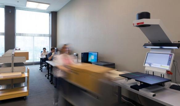 Photo couleur d'une salle comprenant un numériseur grand format sur une table au premier plan, d'une série d'étagères à gauche et de deux personnes assises à des postes de travail en arrière-plan.