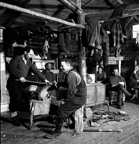 Photo noir et blanc d'hommes se reposant et affûtant leur hache dans un pavillon-dortoir.