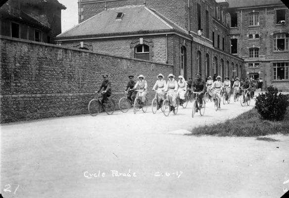 Photo noir et blanc d'hommes et de femmes en uniforme faisant du vélo. Les femmes sont vêtues d'uniformes de couleur pâle avec des ceintures foncées et des chapeaux alors que les hommes portent des uniformes militaires et des chapeaux. Ils pédalent le long d'une route bordée à gauche par un grand mur de briques. Un grand bâtiment aux façades fenêtrées est bien visible à l'arrière-plan. La légende « Cycle Parade » (Défilé à vélo) est inscrite au bas de l'image.