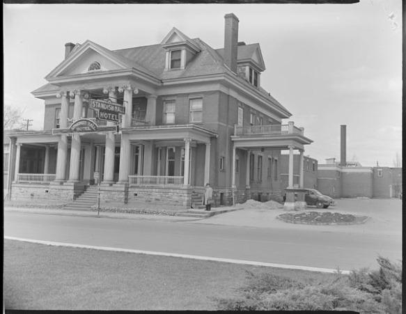 Photo noir et blanc de l'hôtel Standish Hall, à Hull (Québec). Un homme portant un chapeau et un imperméable se tient à la droite du bâtiment, une mallette à la main.