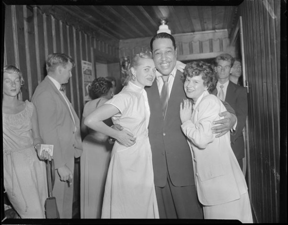 Photo noir et blanc du duc Ellington se tenant entre deux femmes et posant à l'hôtel Standish Hall.