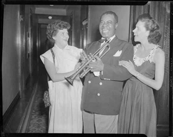 Photo noir et blanc de deux femmes avec un homme tenant une trompette.