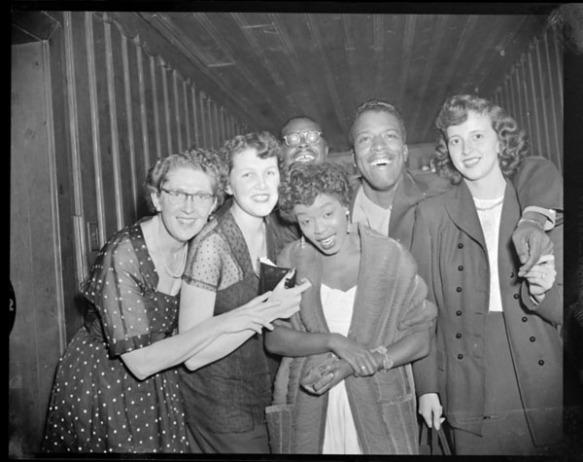 Photo noir et blanc de cinq jeunes personnes rassemblées autour de la chanteuse de jazz américaine Sarah Vaughan pour se faire photographier.