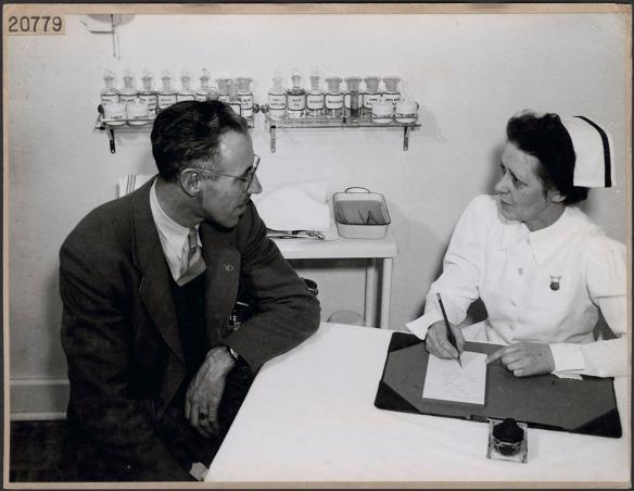 Photo noir et blanc d'une infirmière discutant avec un homme dans un bureau médical et prenant des notes.