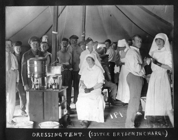 Photo noir et blanc d'infirmières militaires portant des tabliers et des voiles blancs, soignant de nombreux patients dans une tente. Une des infirmières est assise sur une chaise, les pieds et les mains croisés, fixant l'appareil photo. Les deux autres infirmières sont debout, en train de panser les blessures de soldats. Les patients sont pour la plupart vêtus en civil, mais certains sont en uniforme. Du matériel médical, dont des pansements et des seaux, est visible au premier plan et au centre de la photo.