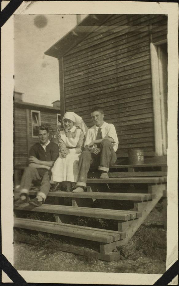 Photo noir et blanc de trois personnes assises sur les marches d'une baraque en bois. Deux hommes portant des chemises légères et des pantalons dont le bas est roulé sont assis de chaque côté d'une infirmière en uniforme. Tous sourient pour la photo.