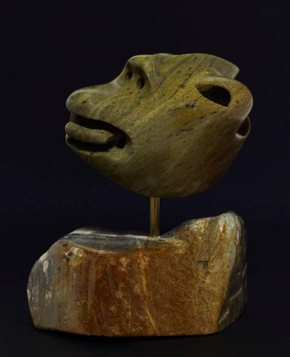 Photo couleur du devant d'une sculpture stylisée d'un homme, la langue sortie.