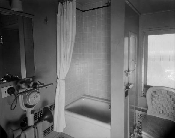 Photo noir et blanc d'une douche, d'un bain et d'une toilette dans une voiture-bar de train.