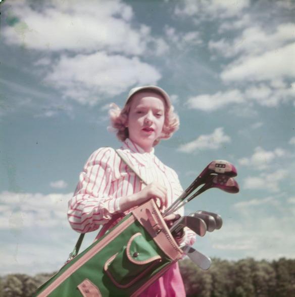 Photo couleur d'une femme transportant ses bâtons de golf sous un ciel bleu partiellement ennuagé.
