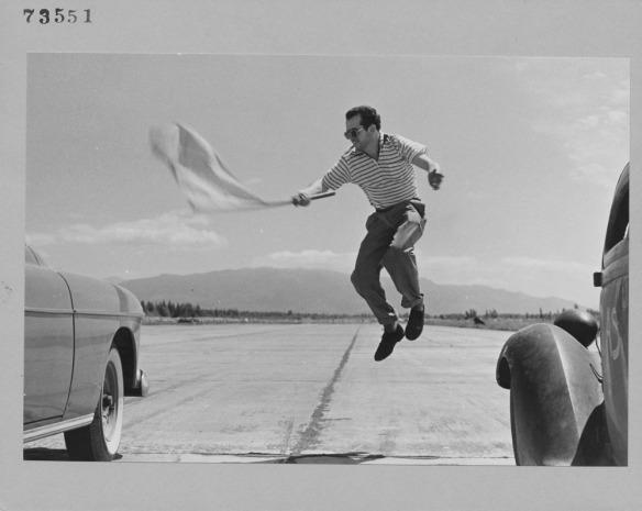 Une photographie noir et blanc d'un homme sautant dans les airs entre deux autos, agitant un drapeau pour donner le signal de départ d'une course.
