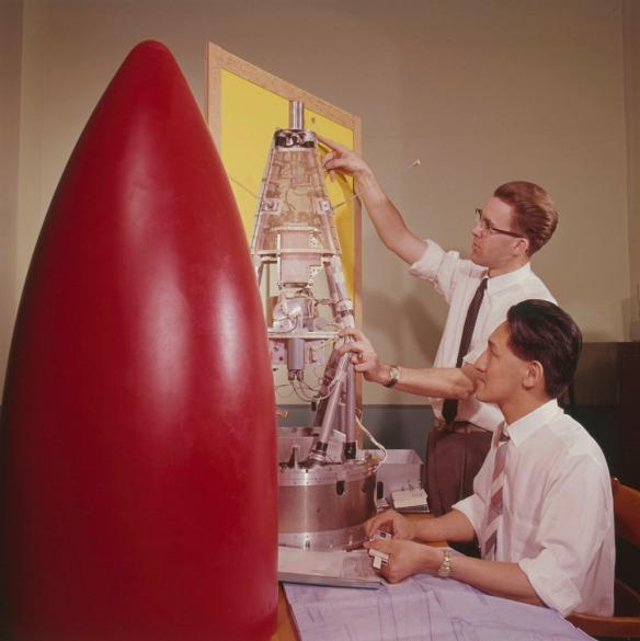 Une photo couleur montrant la coquille rouge d'un projectile tandis que deux hommes travaillent sur l'intérieur à côté
