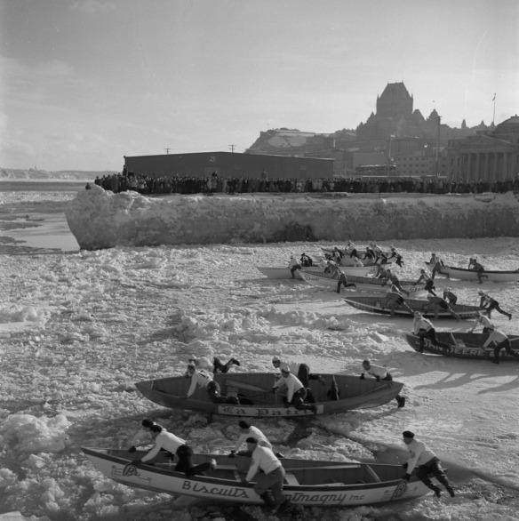 Une photographie noir et blanc de huit équipes poussant leur canot sur les glaces du fleuve en direction de l'eau libre.