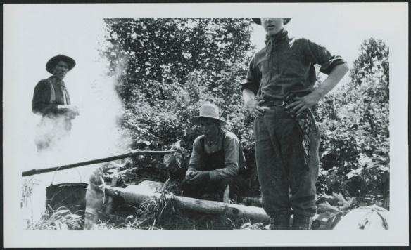 Photo noir et blanc de trois hommes réunis autour d'un feu, prenant probablement une collation en milieu de journée.
