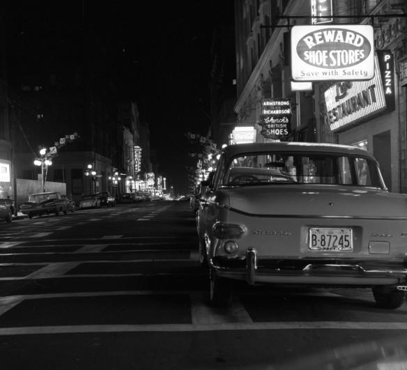 Photo noir et blanc d'une rue pendant la nuit; des voitures sont garées des deux côtés et des enseignes au néon illuminent la rue.