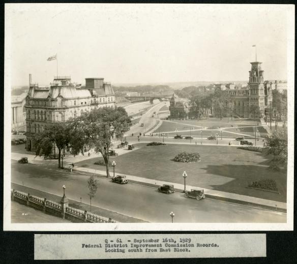 Photo noir et blanc d'un parc calme et des rues environnantes entourés de deux gros immeubles sur lesquels le drapeau de l'Union flotte sur le toit supérieur. Des voitures anciennes sont garées sur la rue principale au premier plan.