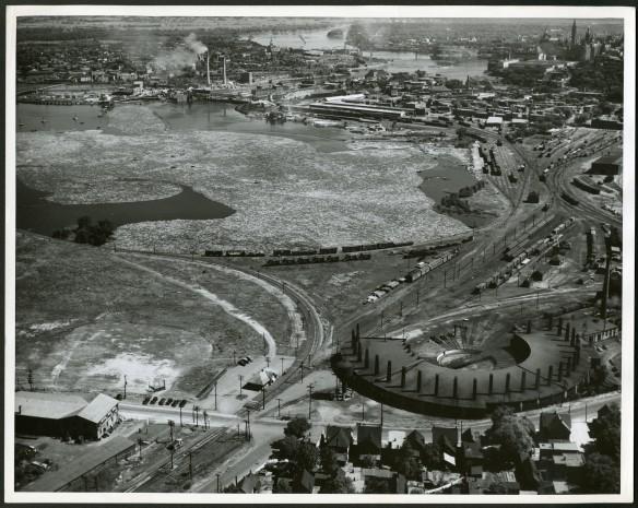 Photo aérienne noir et blanc d'un paysage industriel avec des rondins flottant dans l'eau et une centrale électrique et des lignes ferroviaires au premier plan. En arrière-plan se trouve la cité parlementaire.