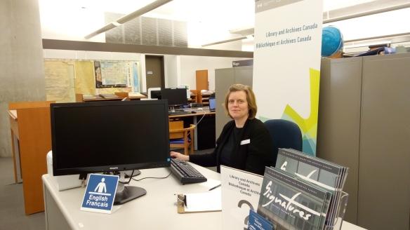 Photo couleur d'une femme assise derrière un bureau de service avec la bannière de Bibliothèque et Archives Canada derrière elle.