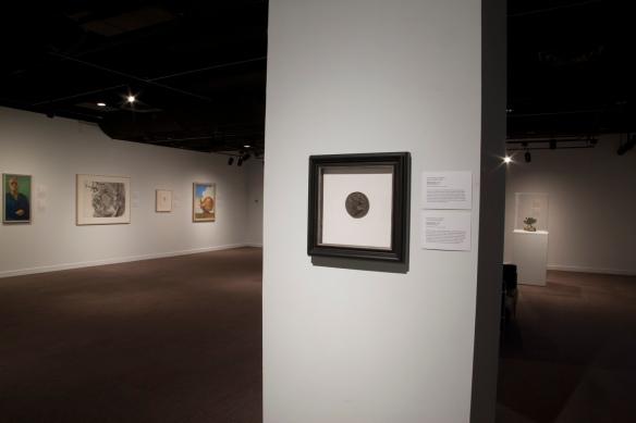 Photo couleur d'une salle faiblement éclairée, diverses œuvres d'art sur les murs.